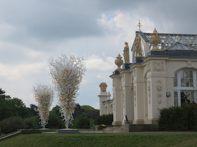 photo-  on left, Chihuly glass sculpture-  2 inverted conesmade up of white and yellow glass tentacles, on right, neo-classical white building (the temperate house at Kew Gardens)