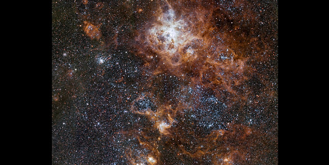 Glowing brightly about 160 000 light-years away, the Tarantula Nebula is the most spectacular feature of the Large Magellanic Cloud, a satellite galaxy to our Milky Way. This image from VLT Survey Telescope at ESO's Paranal Observatory in Chile shows the region and its rich surroundings in great detail. It reveals a cosmic landscape of star clusters, glowing gas clouds and the scattered remains of supernova explosions.  Credit: ESO
