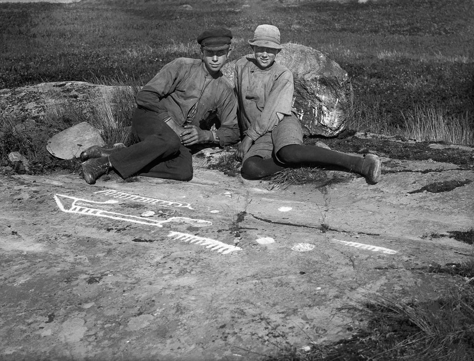 Boys with a prehistoric rock carving from the Bronze Age (c. 1800-500 BC) in Stora Herrebro. 1924.