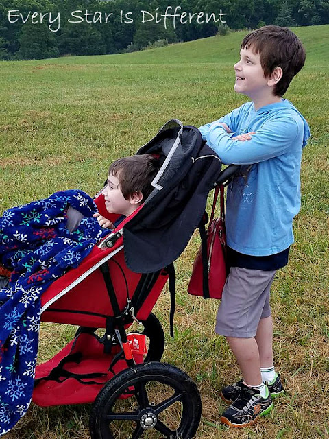 The boys watching hot air balloons set up and take flight.
