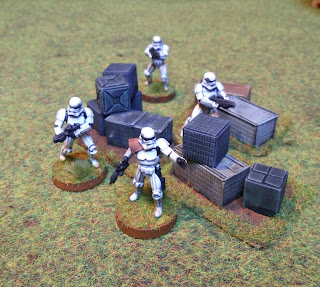 Stormtroopers huddle around cargo boxes