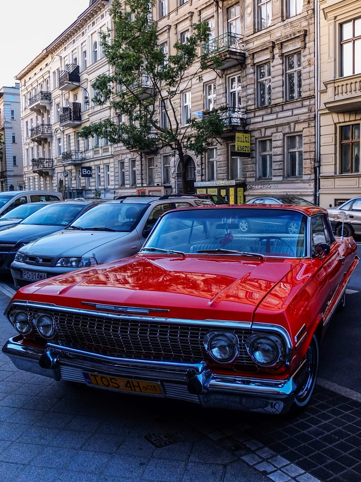 A red Chevrolet parked on the street in Poznań, Poland.