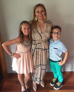 A caucasian woman with gold earrings wearing a long dress. Either side of her are two children. The the left is a girl wearing a pink dress. To the right is a boy with glasses, a blue shirt and green trousers.