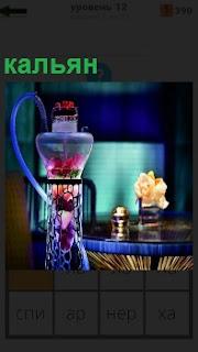 Около стола стоит кальян, прибор для курения, красочно оформленный