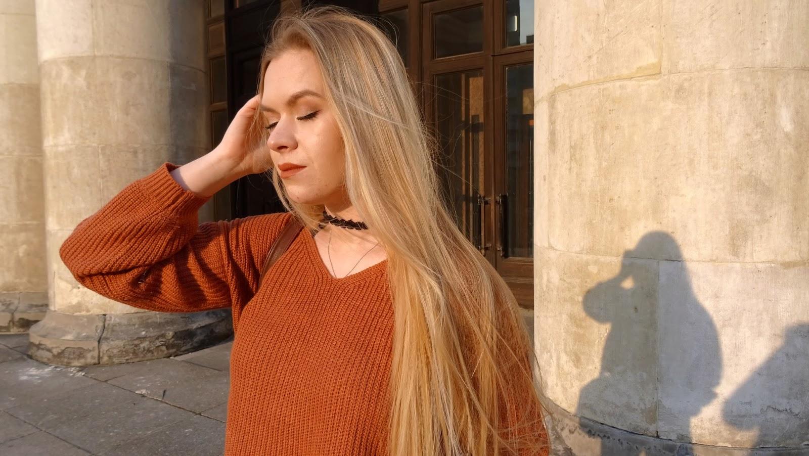 pomarańczowy sweter długie blond włosy