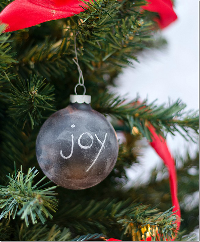 a black chalkboard ball ornament with the word JOY on it on Christmas tree.