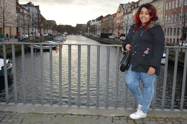 Girl standing my canal in Christianshavn, Copenhagen, Denmark