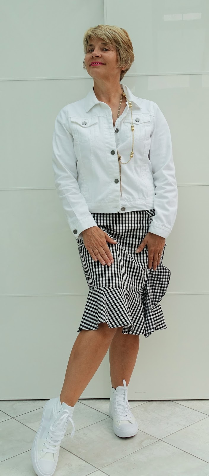 Create a more casual, edgier look to your gingham skirt by adding pristine Converse and a white denim jacket