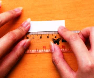 Measure the length of the paper as a circumference of a ring with a millimeter ruler The size you've got will be converted into the size of your ring.