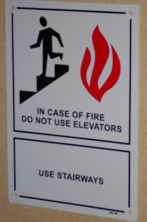 sign reads: in case of fire, do not use elevators, use stairs, has a picture of person using stairs