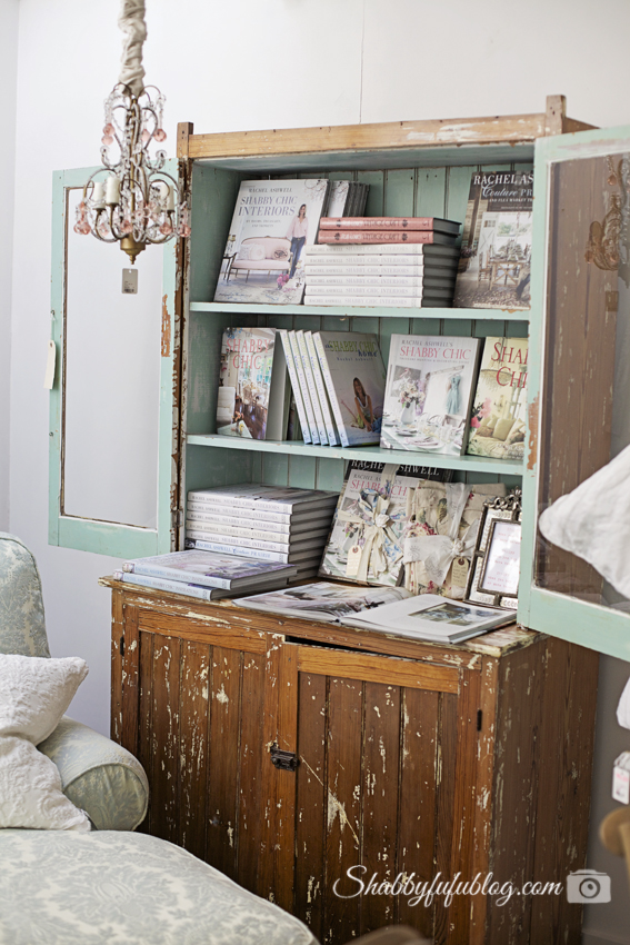 Rachel Ashwell's shabby chic style book collection, displayed in a beautiful distressed wooden china cabinet painted a stunning mint green.