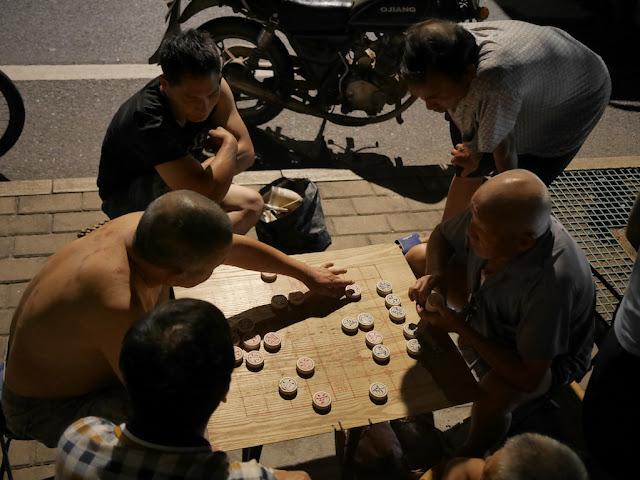 men playing xiangqi at night in Ganzhou, Jiangxi
