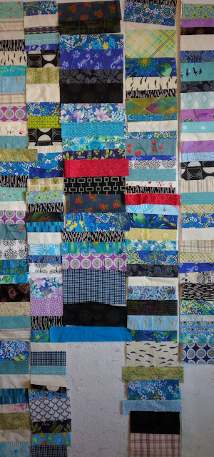 Chinese Coin strips from vintage fabrics are sewn into a quilt top