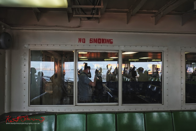 Seating on an open deck section of a Staten Island Ferry, reflections and silhouettes of commuters. No Smoking Sign.  Travel photography by Kent Johnson.