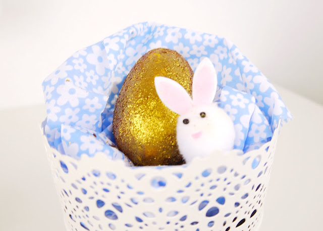 a lush glittery golden egg bath bomb sat on blue floral fabric in a white bucket