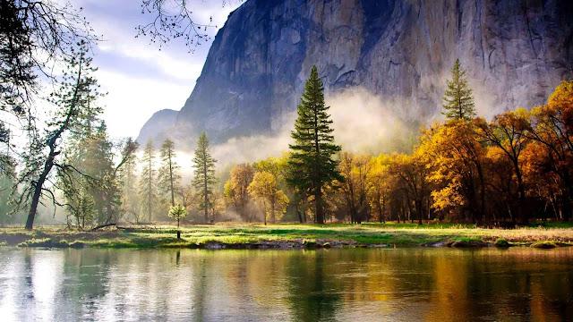 Mooi herfst landschap met rivier en bergen. En mist of laaghangende bewolking.
