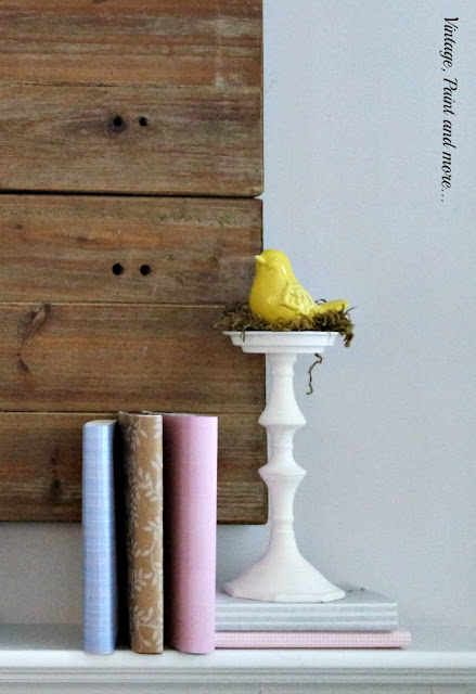 pastel paper covered books with a ceramic bird in a nest for a spring mantel