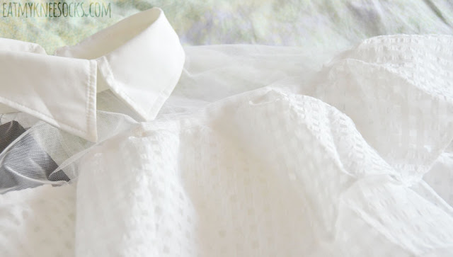 Details on the white sheer mesh paneled collared off-shoulder ruffled top from Twist X Turn.