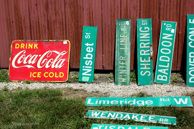 old green street signs leaning on a red barn