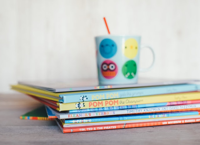 Pile of children's books with a kids cup and straw on top of them