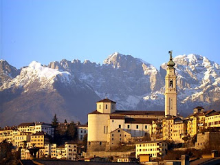 The skyline of Belluno with the Duomo in the foreground  and the Dolomites providing a spectacular backdrop