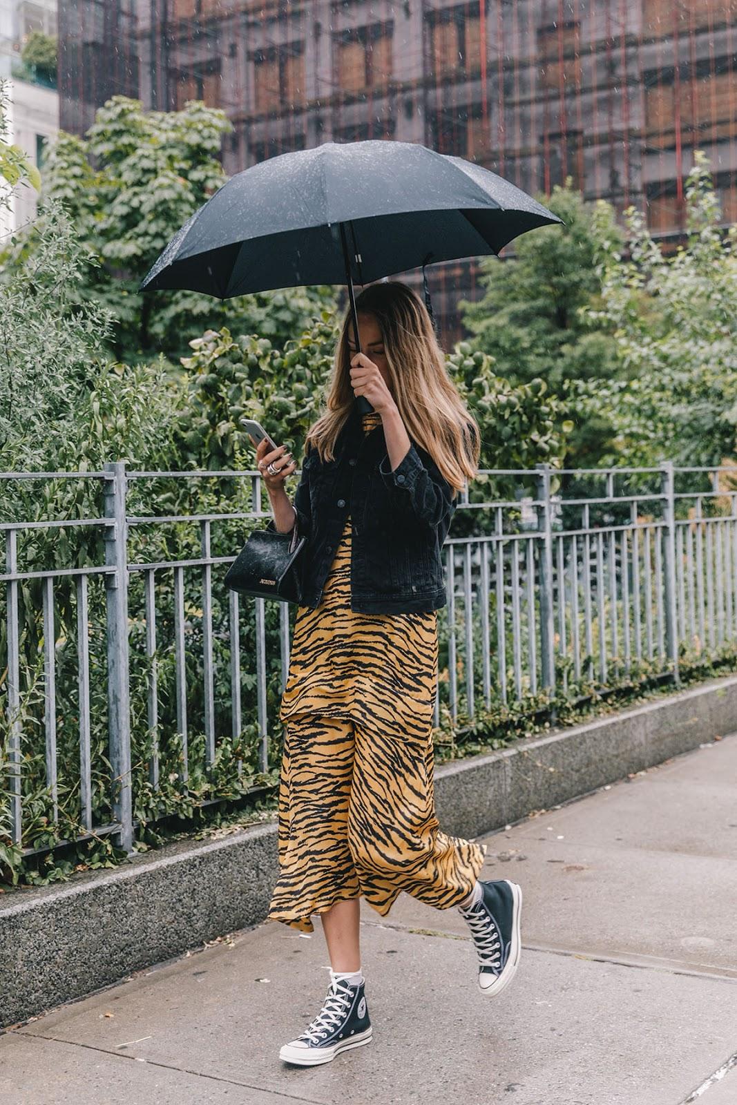 Stylish Rainy Day Outfit Idea: Black Denim Jacket, Black Mini Bag, Animal-Print Dress, and Black Hi-Top Converse Sneakers