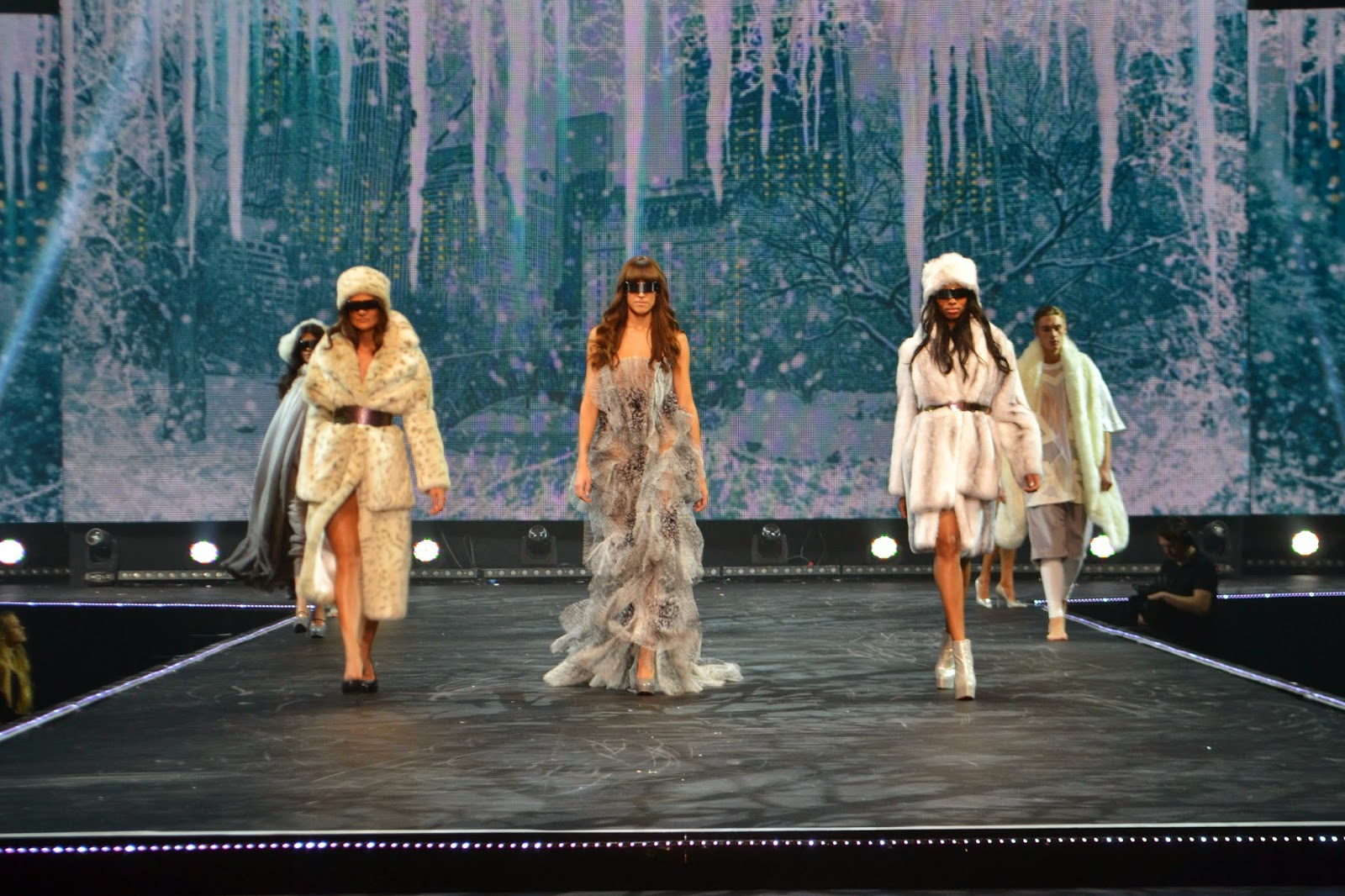 5 models walking down the cat walk wearing winter clothing