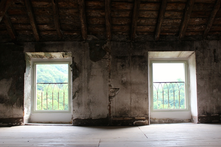Decaying interior room of French Chateau Gudanes with windows overlooking mountains