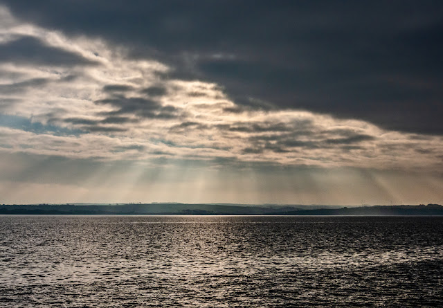 Another shot of the sun breaking through heavy clouds over the Solway Firth