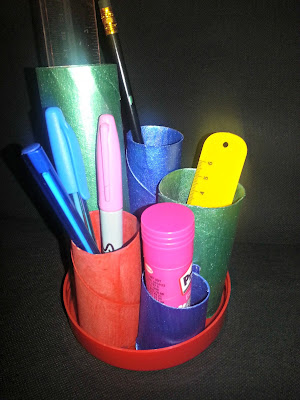 A pencil pot, made from toilet roll tubes and an upturned lid and painted.