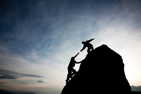 person helping another climb a rock