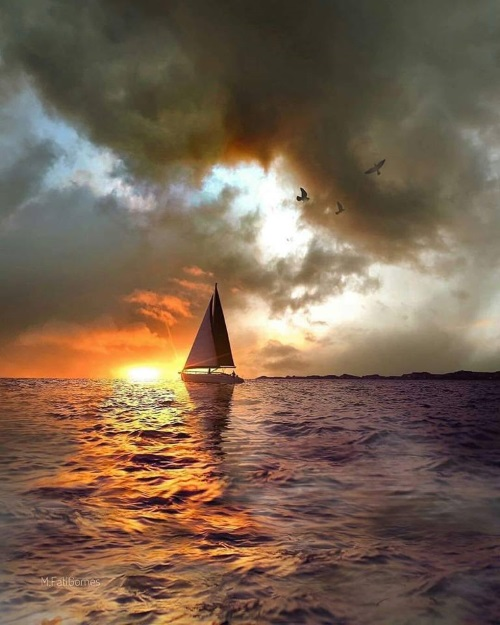 Paisagem do nascer do sol, o mar e um barco ao longe que vem surgindo.