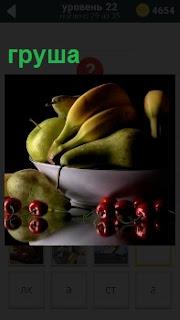 В глубокой тарелке лежат несколько фруктов груша и рядом несколько вишенок с отражением на столе