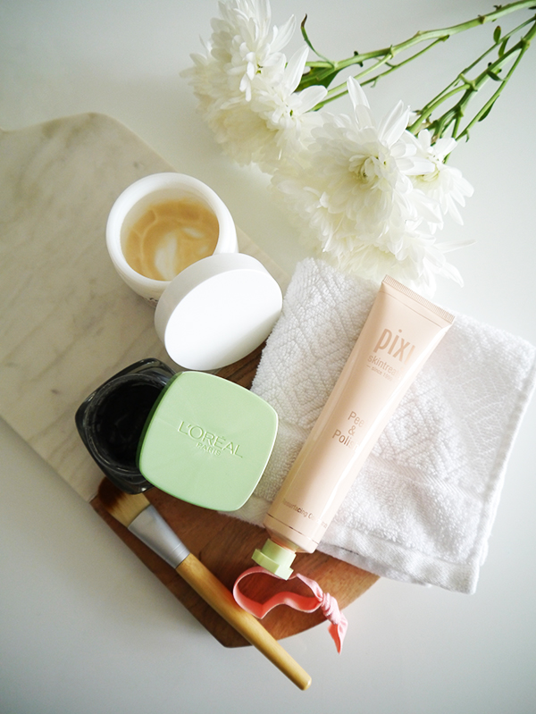 Flat lay featuring Pixi Skintreats Peel & Polish, L'Oreal black clay mask, Fresh Black Tea Instant Perfecting Mask