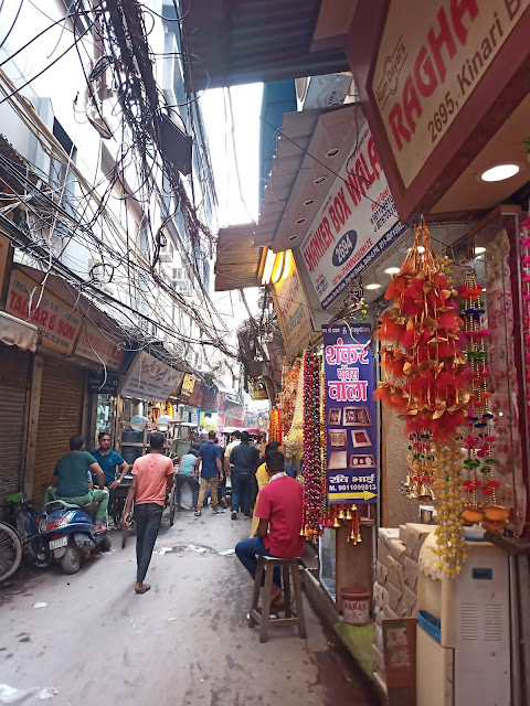 Chandni Chowk laneway with passersby and shopkeepers, and tangle of electricity cables suspended in the sky above