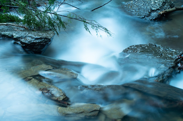 Smooth, silky water pouring over different levels of rocks in a brook, looking almost unreal while green trees poke into view.