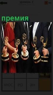 несколько мужчин и одна женщина держат в руках статуэтки в виде премии