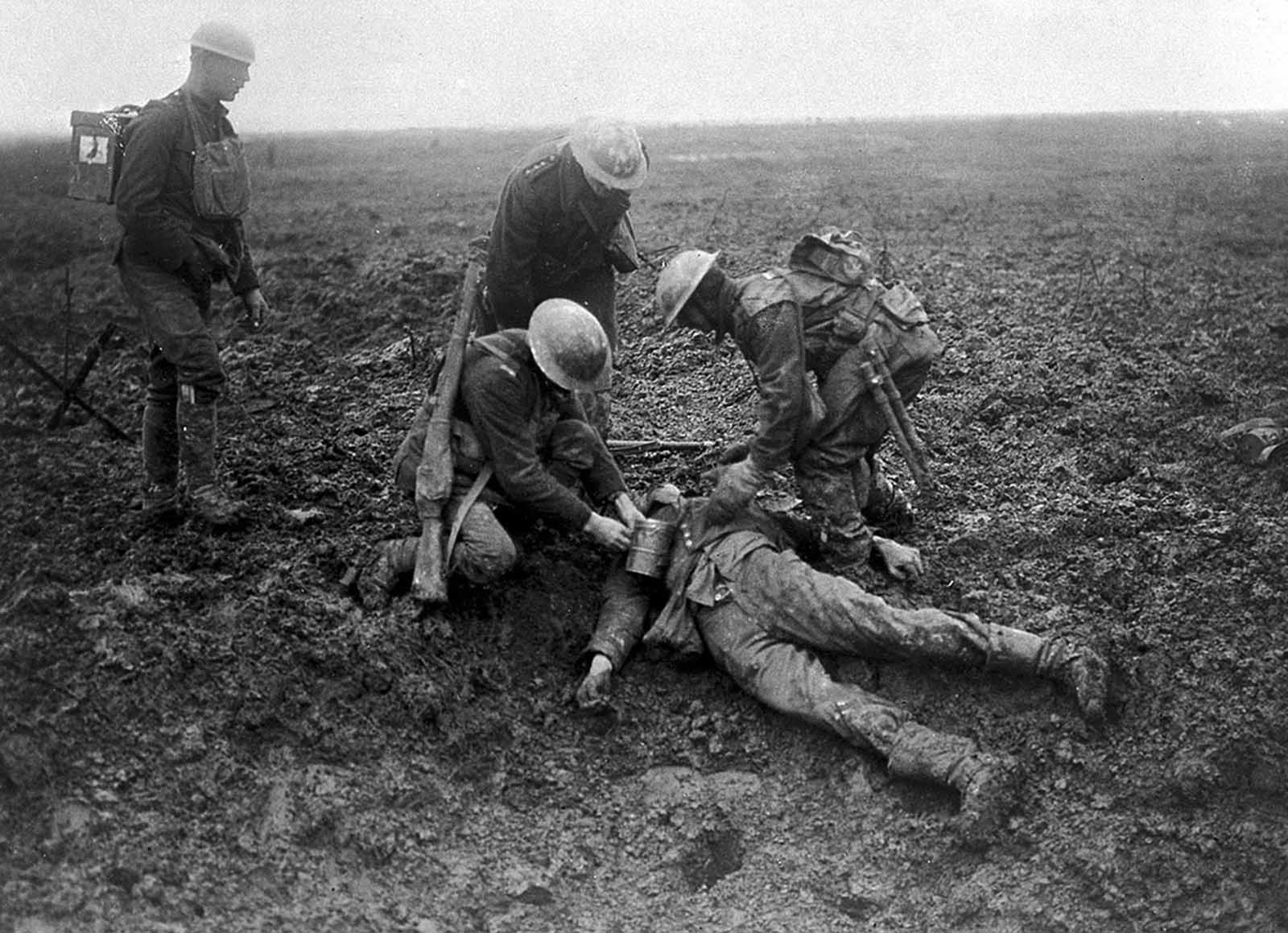 Canadian soldiers tend to a fallen German on the battlefield at the Battle of Vimy Ridge in 1917.