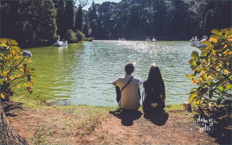 Casal sentado na beira do lago negro