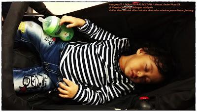 gambar kanak-kanak perempuan tidur atas stroller bayi setelah diberi minum ubat tidur di Hospital Serdang memakai baju belang hitam putih dan seluar jeans denim.