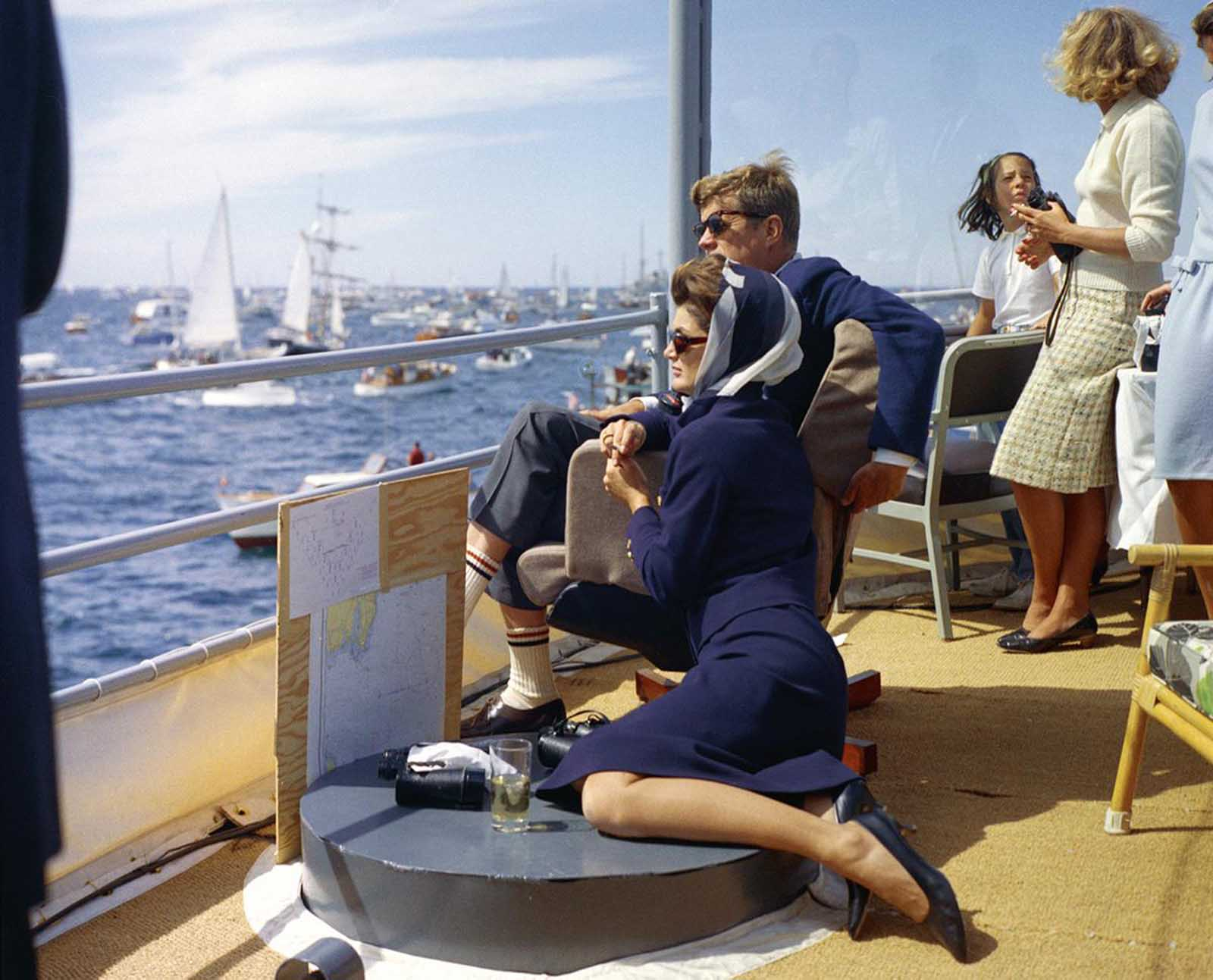 Aboard the USS Joseph P. Kennedy, Jr., named after the brother killed in World War II, President and Mrs. Kennedy watch the first race of the 1962 America's Cup competition off Newport, Rhode Island.