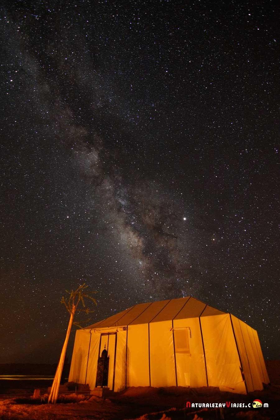 Via láctea sobre Jaima en las dunas de Erg Chebbi, Merzouga, Marruecos