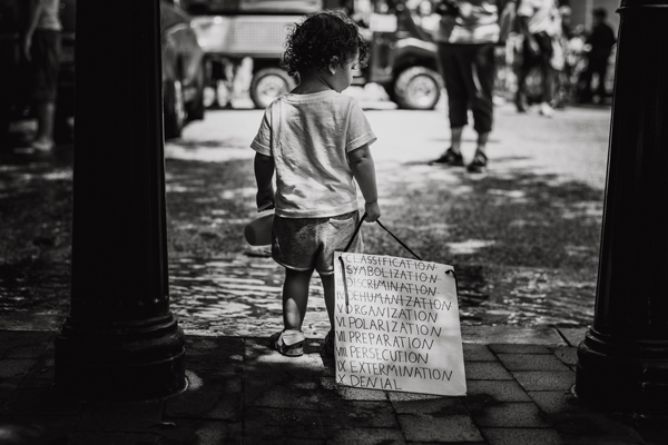 black and white image of a young child standing on a sidewalk, holding a sippy cup in one hand and a sign reading