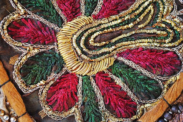 Detail van Indiaas wandkleed met een geborduurde bloem en gouddraad.