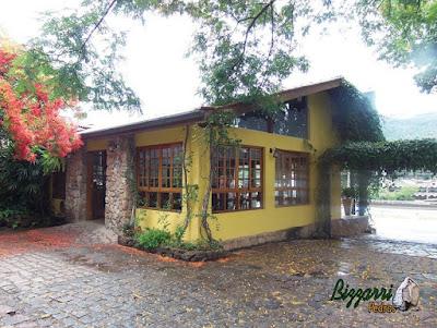 Fachada do restaurante Recanto das Pedras com as paredes de pedra, alicerces de pedra com o piso de pedra bruta com a execução do paisagismo com o flamboyant florido.