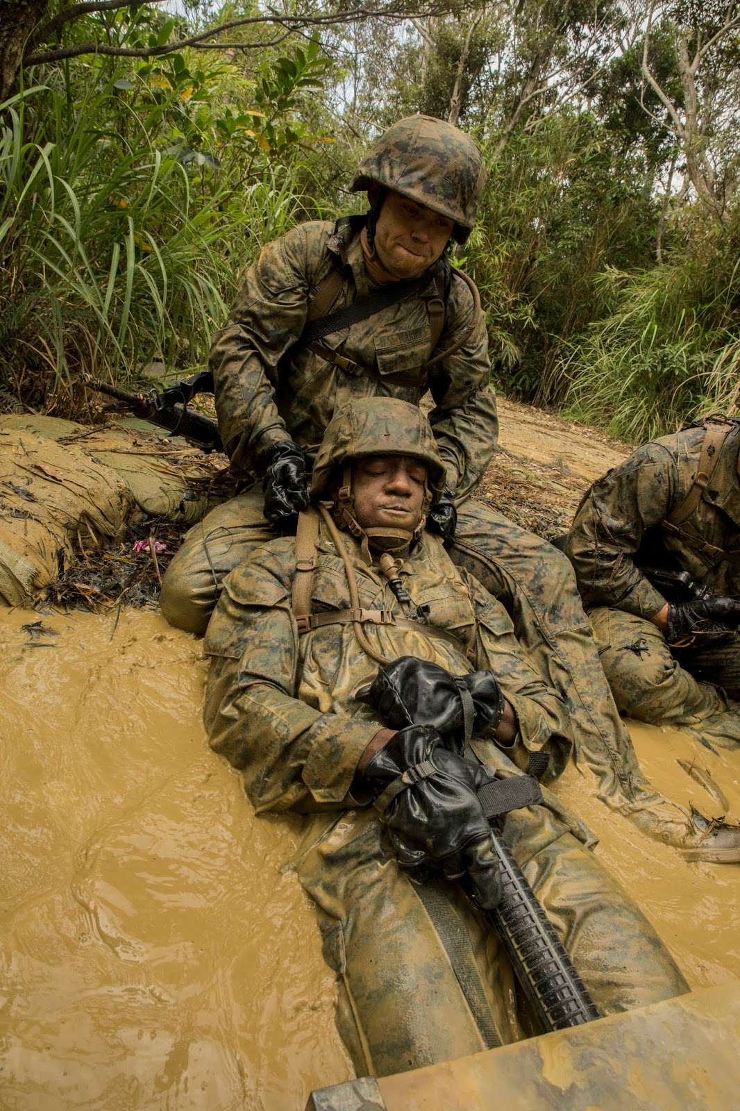 Two men in military gear. One is pulling the other out of a dirty river onto a muddy bank.