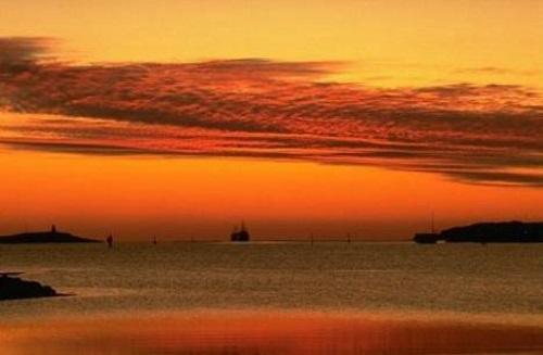 Barco soprado pela brisa do amanhecer no mar. #PraCegoVer