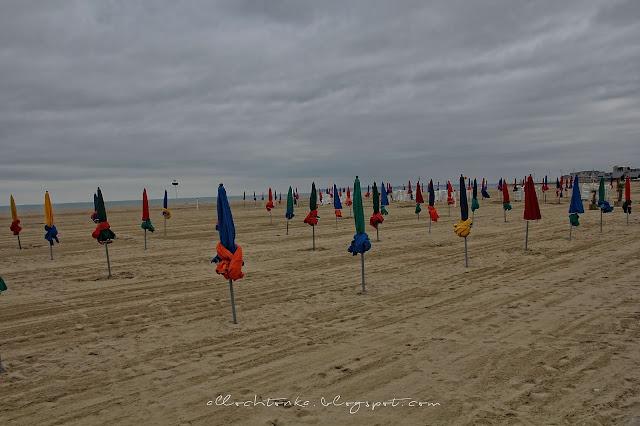 kolorowe parasole na plaży w Deauville