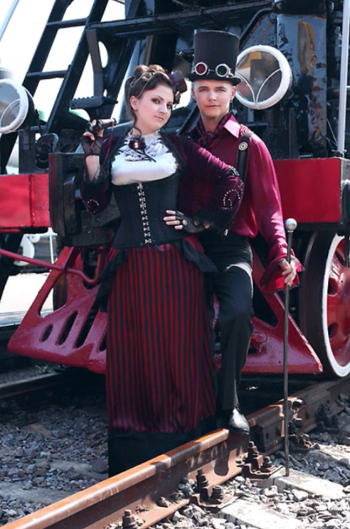 Coordinated steampunk couple, man in top hat, suspenders, goggles, can. woman wearing stiped skirt, corset, blouse and bolero. matching steampunk costumes for couples