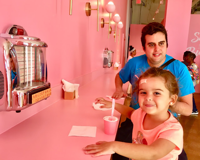 Toddler and her dad enjoy small milkshakes in front of a small jukebox
